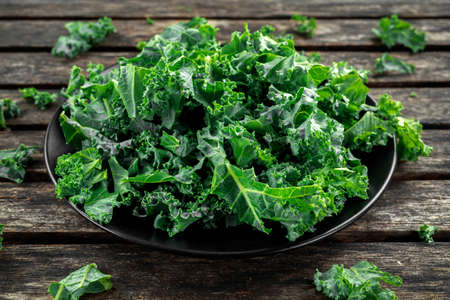 Fresh green healthy superfood vegetable kale leaves in a black plate on wooden rustic table