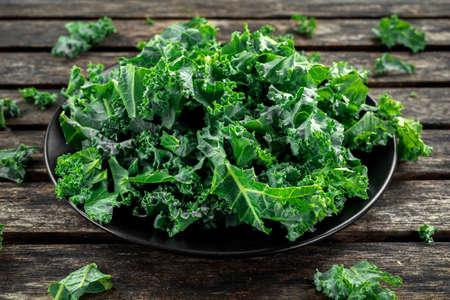 나무 소박한 테이블에 검은 접시에 신선한 녹색 건강 superfood 야채 양배추 잎
