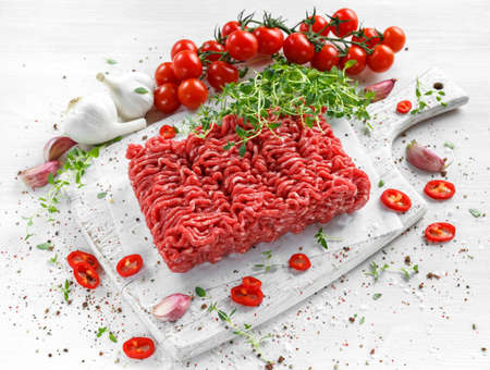 Fresh Raw Beef Minced Meat with salt, pepper, chilli and fresh thyme on white board. Imagens