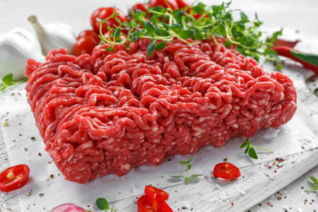 Fresh Raw Beef Minced Meat with salt, pepper, chilli and fresh thyme on white board. Stock Photo