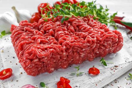 Frisches rohes Rindfleisch-gehacktes Fleisch mit Salz, Pfeffer, Paprikas und frischem Thymian auf weißem Brett. Standard-Bild