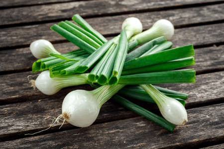 Raw Bunch of fresh spring onion on rustic wooden table Stok Fotoğraf