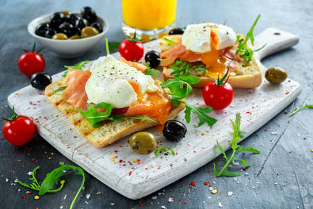Gepocheerd ei op gegrilde toast met gerookte zalm, rucola, olijven, groenten en sinaasappelsap. op wit bord. gezond ontbijt