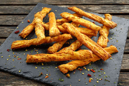 Cheese twist, sticks, snack with herbs on stone board.
