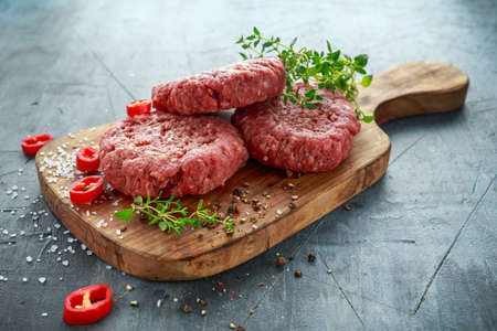 Home HandMade Raw Minced Beef steak burgers on wooden board. Stock Photo