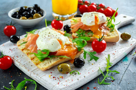 Poached egg on grilled toast with smoked salmon, rucola, olives, vegetables and orange juice. on white board. healthy breakfast