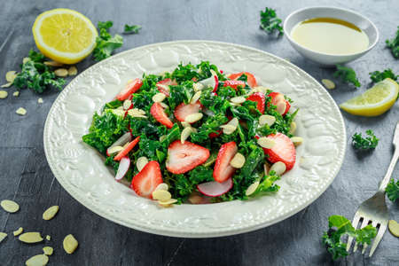 Healthy kale salad with strawberries and almond in a white plate