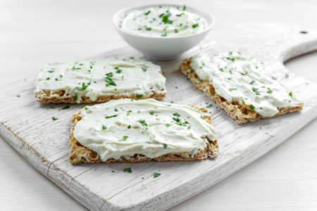Homemade Crispbread toast with Cream Cheese and parsley on white wooden board background.