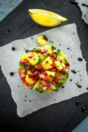 Tuna sushi stacks with mango, cucumber, tomatoes salsa served with balsamic vinegar, nigela ans sesame seeds