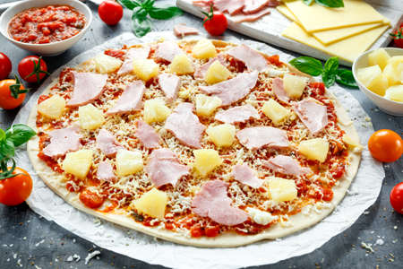 Ready to cook hawaii pizza with ham and pineapple, basil, tomatoes on backed paper