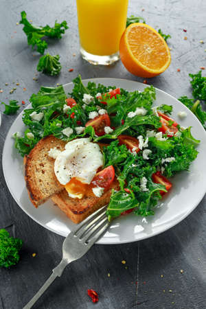 Breakfast Green Kale with poached eggs, feta cheese, tomatoes and toast. healthy food