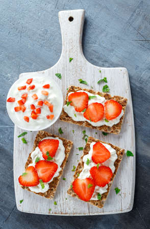 Homemade Crispbread toast with Cottage Cheese and Strawberry on white wooden board.