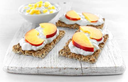 カッテージ チーズとホワイト木製ボードにネクタリンと自家製のクリスプブレッド トースト。