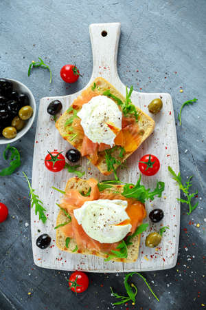 Poached egg on grilled toast with smoked salmon, rucola, olives and vegetables on white board. healthy breakfast Reklamní fotografie