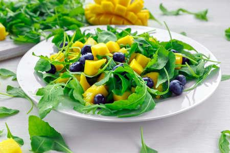 Mango, blueberries salad with arugula on white plate
