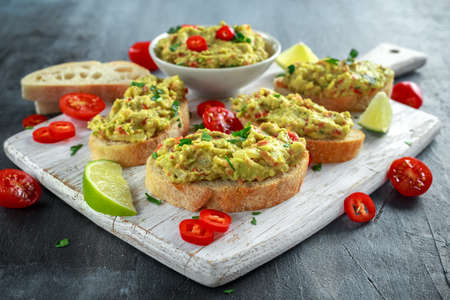 Homemade Guacamole toast with chili pepper, parsley on white wooden board Stock Photo