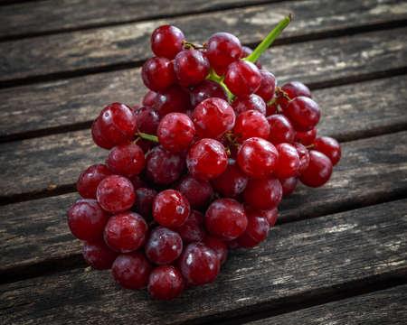 Uva roja madura. Rosa manojo en una vieja mesa de madera rústica Foto de archivo - 82572231