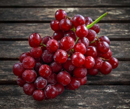 Ripe red grape. Pink bunch in a old rustic wooden table