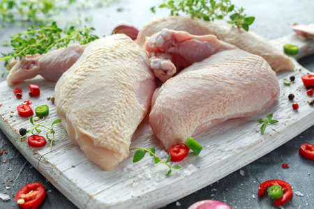 Raw Chicken breast supremes fillets with chilli, pepper corns and thyme on white wooden chopping board Zdjęcie Seryjne