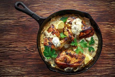 Creamy chicken fellets supremes in mushroom sauce with parsley In rustic cast iron skillet. Banco de Imagens - 82446828