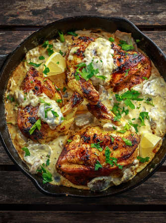 Creamy chicken fellets supremes in mushroom sauce with parsley In rustic cast iron skillet.