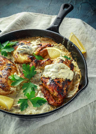 Creamy chicken fellets supremes in mushroom sauce with parsley In rustic cast iron skillet. Banco de Imagens - 82752889