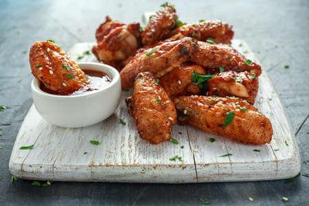 참 깨와 흰색 나무 보드에 달콤한 칠리 소스와 구운 된 닭 날개. 스톡 콘텐츠
