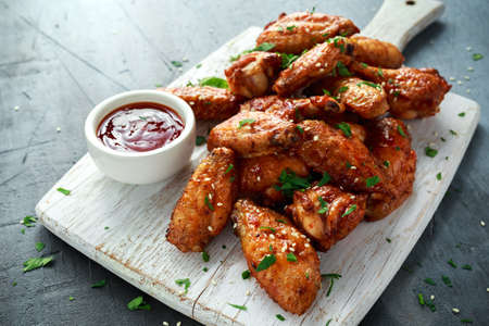 Baked chicken wings with sesame seeds and sweet chili sauce on white wooden board.