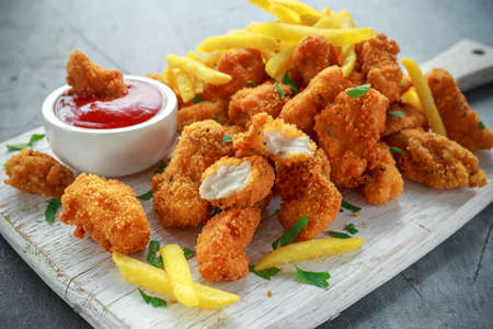 Fried crispy chicken nuggets with french fries and ketchup on white board Banco de Imagens - 83006739
