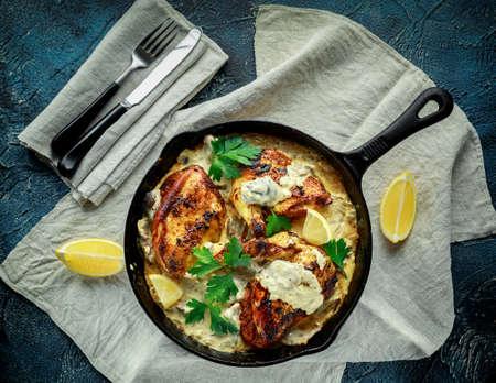 Creamy chicken fellets supremes in mushroom sauce with parsley In rustic cast iron skillet. Banco de Imagens - 82940126