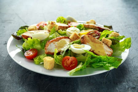 Fresh healthy Caesar salad with chicken, egg quail, tomatoes, Cheese and Croutons in a white plate Imagens