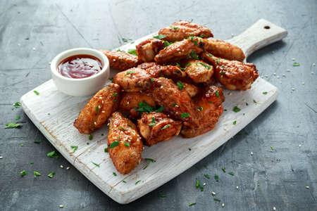 Gebakken kippenvleugels met sesamzaden en zoete chili saus op witte houten bord.