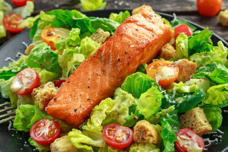 Caesar Salmon Salad with croutons, parmesan cheese, tomatoes, dressing and pepper in a black plate on wooden table.
