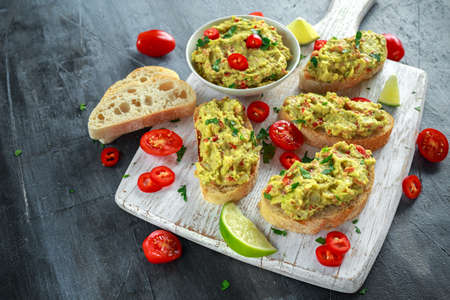 Homemade Guacamole toast with chili pepper, parsley on white wooden board Stock Photo - 83823771