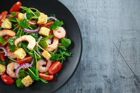 신선한 건강한 새우 토마토, 검은 접시에 붉은 양파와 샐러드. 개념 건강 식품