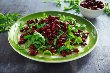 Red beans and wild rocket healthy salad in a green plate