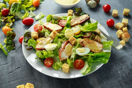Fresh healthy Caesar salad with chicken, egg quail, tomatoes, Cheese and Croutons in a white plate Stock Photo