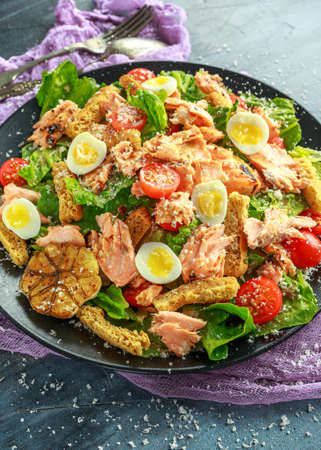 Cesar salad with salmon, cherry tomatoes, garlic, crutons, romaine lettuce and parmesan.