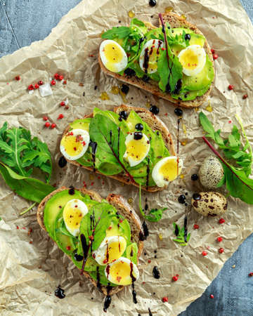 huevos de codorniz: Healthy Avocado and quail eggs toasts with wild rocket and sea salt