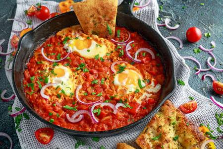 Smakelijk ontbijt Shakshuka in een ijzeren pan. Gebakken eieren met tomaten, rode, gele paprika, ui, peterselie, pitabroodje en kruiden. Gezond eten Stockfoto - 85765565