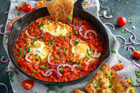 Tasty Breakfast Shakshuka in a Iron Pan. Fried eggs with tomatoes, red, yellow peppers, onion, parsley, Pita bread and herbs. Healthy Food 版權商用圖片 - 85765565
