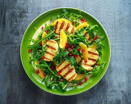 구운 된 Halloumi 치즈 샐러드 오렌지, 로켓 단풍, 석류와 호박 씨앗. 건강 식품