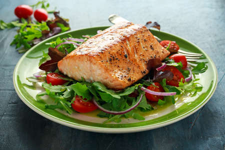 Baked salmon steak with tomato, onion, mix of green leaves salad in a plate. healthy food Zdjęcie Seryjne