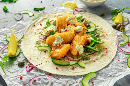 Fresh Fish Tortilla with cucumber, red onion, Capers, lemon, salad leaves and tartare sauce. Healthy Food