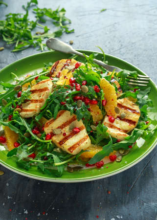 Grilled Halloumi Cheese salad with orange, rocket leaves, pomegranate and pumpkin seed. healthy food