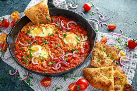 Smakelijk ontbijt Shakshuka in een ijzeren pan. Gebakken eieren met tomaten, rode, gele paprika, ui, peterselie, pitabroodje en kruiden. Gezond eten