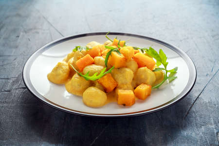 Homemade Butternut squash gnocchi with wild rocket in a plate 스톡 콘텐츠