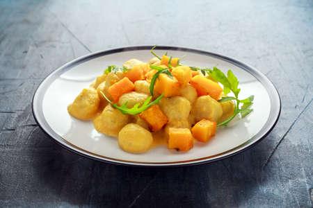 Homemade Butternut squash gnocchi with wild rocket in a plate Archivio Fotografico
