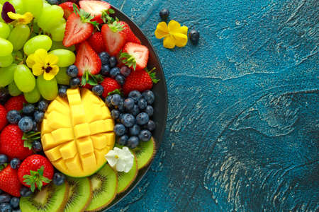 Colorful Mixed Fruit platter with Mango, Strawberry, Blueberry, Kiwi and Green Grape. Healthy food