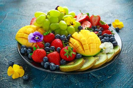 Kleurrijke gemengde fruitschaal met mango, aardbei, bosbes, kiwi en groene druif. Gezond eten